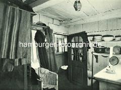 Historische Bilder aus dem Hamburger Gängeviertel - Wohnung im Langen Gang; Garderobe mit Mänteln, Korbstuhl - ein Öllampe brennt auf dem Tisch, im Regal Töpfe und Teller / Schüssel.