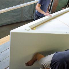 Reinigung vom Schiffsrumpf mit  Wachstüchern vor dem Lackieren - entfernen von möglichen Staubresten.