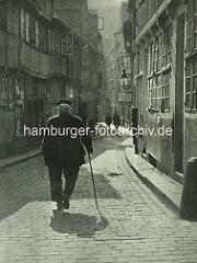 Alte Fotos aus dem Gängeviertel Hamburgs - alter Mann mit Stock im Gegenlicht / Schulgang.