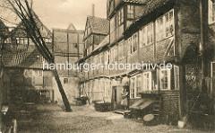 Historische Bilder aus dem Hamburger Gängeviertel - Hinterhof Großer Bäckergang; Frau mit Kind auf dem Arm steht in der Tür, Wäsche auf der Leine.
