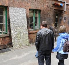 Besucher / Touristen im Hamburger Gängeviertel - Informationsschild.
