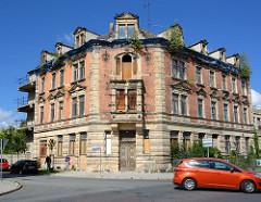 Verfallenes Mietshaus aus der Gründerzeit - junge Birken wachsen in der Dachrinne, vernagelte Fenter und Türen.