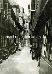 Historische Bilder aus dem Hamburger Gängeviertel - Krameramtswohnungen in Krayenkamp - Bänke mit Blumen / Pflanzen drei Frauen stehen vor der Tür.