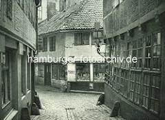 Alte Fotos aus dem Gängeviertel Hamburgs - Prellsteine / Kopfsteinpflaster im Ebraergang - Lebensmittelgeschäft mit Konserven, Schild Maggi.