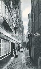 Historische Bilder aus dem Hamburger Gängeviertel - die EinwohnerInnen der Häuser im Brauerknechtsgraben stehen auf der STrasse - einige blicken aus den Fenstern.
