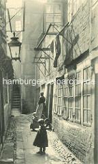 Historische Bilder aus dem Hamburger Gängeviertel - Gang in der Spitaler Strasse; Kinder in Kleidchen, Frau mit Schürze - Gaslaterne und Holzgestelle an der Hauswand vor den Fenstern zum Trocknen der Wäsche.
