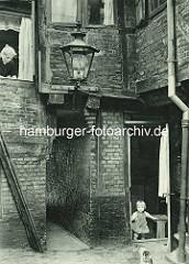 Historische Bilder aus dem Hamburger Gängeviertel - kleines Mädchen mit Katze, die Mutter blickt aus dem Fenster im Langen Gang.