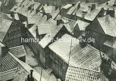 Alte Fotos aus dem Gängeviertel Hamburgs -  schneebedeckte Hausdächer beim Schulgang.