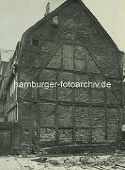Alte Fotos aus dem Gängeviertel Hamburgs -  Fachwerkfassade mit Kontouren eines abgerissenen Hauses im Kornträgergang.