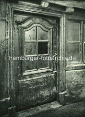 Alte Fotos aus dem Gängeviertel Hamburgs - alte Haustür mit Schnitzerei und kaputtem Fenster im Langen Gang.