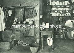 Historische Bilder aus dem Hamburger Gängeviertel - Küche im Breiten Gang; Holzherd in der Herdnische, Feuerholz. Unter dem Regal für Geschirr in Waschbecken.
