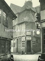 Alte Fotos aus dem Gängeviertel Hamburgs - Kneipe mit Schildern Holsten Bier Ecke Schulgang / Ebraeer Gang.