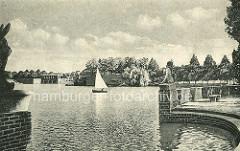 Liebesinsel im Hamburger Stadtparksee - Blick zur Stadthalle, ein Segelboot auf dem Wasser.