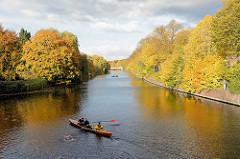Blick von der Streekbrücke auf die Alster in Hamburg Winterhude / Eppendorf - Herbstbäume am Ufer, ein Ruderboot fährt Richung Isebekkanal.