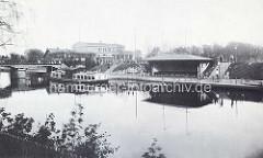 Altes Foto vom Anleger Winterhuder Fährhaus mit Wartehäuschen aus Holz und Alsterdampfer - im Hintergrund das Winterhuder Fährhaus im Hamburger Stadtteil Winterhude.