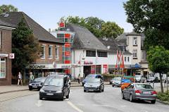 Einkaufsstrasse in Reinbek, Bahnhofsstrasse; Einzelhäuser mit Geschäften - fahrende PKW / Autos.