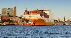 Das RoRo Frachtschiff Grande Angola verlässt den Hambuger Hafen; mit Hilfe von Schleppern wird der Frachter in die Fahrrinne geschleppt. Links das Hafenkrankenhaus und die Hochhäuser an der Bernhard Nocht Strasse von Hamburg St. Pauli.
