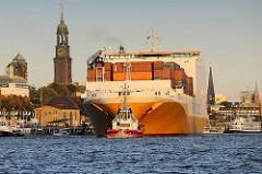 Das RoRo Frachtschiff Grande Angola verlässt den Hambuger Hafen; mit Hilfe von Schleppern wird der Frachter in die Fahrrinne geschleppt. Links vom Schiff die Kuppel vom alten Elbtunnel und der Kirchturm der St. Michaeliskirche - re. Fahrgastschiffe a