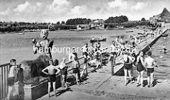 """Kinder in der Badeanstalt, Freibad im Hamburger Stadtpark - Bronzkulptur """"Zentauren Triton + Nereide"""" am Hamburger Stadtparksee - Georg Wrba; Bronze 1912. Im Hintergrund am Seeufer das Parkcafé."""