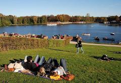 Liegewiese am Hamburger Stadtparksee im Herbst - die Bäume sind herbstlich gefärbt.