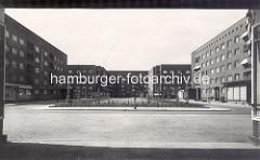 Historische Ansicht vom Semperplatz in der Hamburger Jarrestadt; frisch gepflanzte Bäume. im Hintergrund das Wohngebäude entworfen von den Architekten Grell &  Pruter; das rechte Gebäude wurde vom Architekten Robert Friedmann entworfen, den Entw