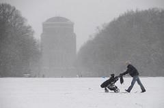 Ein Spaziergänger schiebt einen Kinderwagen im Schneefall über die Große Wiese im Hamburger Stadtpark.
