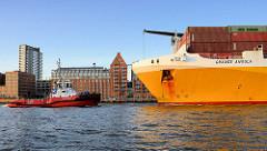 Das RoRo Frachtschiff Grande Angola verlässt den Hambuger Hafen; mit Hilfe von Schleppern wird der Frachter in die Fahrrinne geschleppt. Im Hintergrund die Speichergebäude und Bürohäuser an der Grossen Elbstrasse.