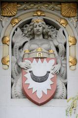 Kieler Wappen - Jugendstildekor an einer Hausfassade; eine Nixe mit Fischschwanz und barem Busen hält das Wappen; goldenes Muscheldekor.