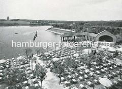Terrasse mit Tischen und Stühlen am Hamburger Stadtparksee; im Hintergrund die Kaskaden und das Planetarium.