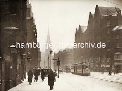 Historisches Bild aus der Hamburger Altstadt - die Mönckebergstrasse / Domhof im Winter, Fussgänger mit Mantel - Schnee liegt auf der Strasse; Strassenbahn und PKW; im Hintergrund der Turm vom Hamburger Rathaus.