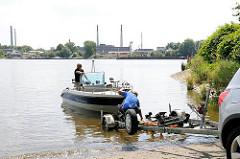 Ein Sportboot wird von einem Trailer auf der Slipanlage im Elbpark Entenwerder zu Wasser gelassen - auf der anderen Seite der Norderelbe Industrieschornsteine und Gebäude auf der Peute in Hamburg Veddel.