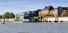 Blick über den Müggenburger Zollhafen im Hamburger Stadtteil Veddel - Herbstbäume an der Promenade; schwimmendes Gebäude vom IBA Dock  - lks. eine Tonne zur Kennzeichnung von Gefahrenstellen aus dem Kardinalsystem; die Gefahrenstelle muss südlich umf