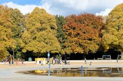 Sonniger Herbsttag in der Hansestadt Hamburg - hohe Bäume im Stadtpark Winterhude in unterschiedlicher Herbstfärbung; Kinder spielen beim Planschbecken auf dem Kinderspielplatz.