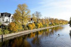 Herbstbäume und Sträucher mit herbstlich gefärbtem Laub am Ufer der Alster am Leinpfad in Hamburg Winterhude - Ruderboot auf dem Wasser.