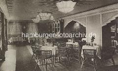 Innenansicht vom Winterhuder Fährhaus - Art Deco Lampen an der Decke, Korbstühle u. Tische mit Tischdecken.