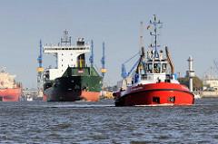 Schiffsverkehr auf der Elbe im Hamburger Hafen - ein Schlepper und Frachtschiff fahren elbabwärts - im Hintergrund liegt ein Schiff im Dock der Werft.