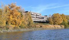 Herbstbäume am Ufer vom Hovekanal im Gewerbegebiet auf der Peute von Hamburg Veddel - historische Industriearchitektur.