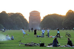 Abenddämmerung im Hamburger Stadtpark - Parkbesucher sitzen auf der Grossen Wiese und Grillen; im Hintegrund das Planetarium,