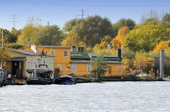 Hausboote am  Berliner Ufer im Hamburger Spreehafen, Holzboot / gelbes Hausschiff - im Hintergrund Herbstbäume in Hamburg Wilhelmsburg.
