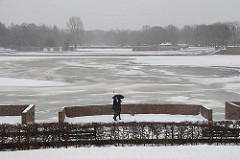 Spaziergänger mit Regenschirm am Stadtparksee in Hamburg Winterhude - der See ist zugefroren.