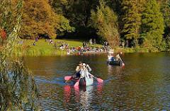 Kanus auf dem Stadtparksee in der Herbstsonne - die Blätter der Bäume sind herstlich gefärbt; Bilder aus Hamburg Winterhude.