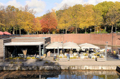 Ehem. Hafenanlage beim Goldbekkanal am Eingang vom Stadtpark in Hamburg Winterhude - Restaurant / Café auf dem Ponton, BesucherInnen sonnen sich - Herbstbäume im Hintergrund an der Saarlandstrasse.