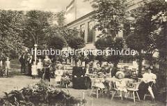 Biergarten, Gartenkaffee am Winterhuder Fährhaus; Erwachsene und Kinder mit Strohut sitzen an den Tischen - eine Frau mit Fahrrad steht auf dem Weg.