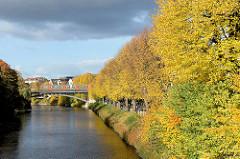 Blick von der Görnebrücke auf die Alster in Hamburg Winterhude - im Hintergrund die Hochbahnbrücke über den Hamburger Fluss; Herbstbäume am Alsterufer / Leinpfad.