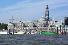 Elbufer in der Hamburger Neustadt - Segelschiffe liegen am Ponton, Touristen auf der Promenade - eine Hochbahn fährt auf dem Viadukt Richtung Rödingsmarkt. Hinter dem Verlagsgebäude von Gruner + Jahr am Baumwall der Kirchturm der St. Michaeliskirche.