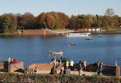 Boote auf dem Stadtparksee - ParkbesucherInnen stehen in der Herbstsonne bei den Kaskaden - herbstlich gefärbte Bäume im Park.