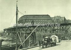 Historische Hamburger Darstellung - ein hoch beladener Pferdewagen steht am Ufer des Binnenhafens am Kajen - eine Hochbahn fährt auf dem Viadukt in den Rödingsmarkt ein. Im Hintergrund das Slomannhaus und der Elbhof.