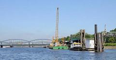 Ponton mit Arbeitsschiffen / Schwimmkran in der Norderelbe bei Hamburg Rothenburgsort, Entenwerder. Re. die bewegliche Wasserbrücke, die sich den Gezeiten / Tide anpasst. Im Hintergrund die Elbbrücke und die Freihafen-Elbbrücke.