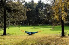 Goldener Herbsttag im Hamburger Stadtpark - ein Besucher hat die Hängematte aufgehängt und sonnt sich - Bereich vom historischen Sprunggarten.