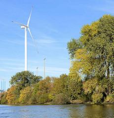 Blick vom Köhlbrand / Süderelbe auf die Windkraftanlage von Hamburg Wasser im Hamburger Stadtteil Steinwerder; Herbstbäume säumen das Wasser vom Elbufer.